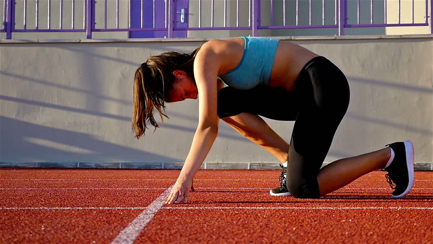 Track runner woman preparing to run at starting line, slow motion