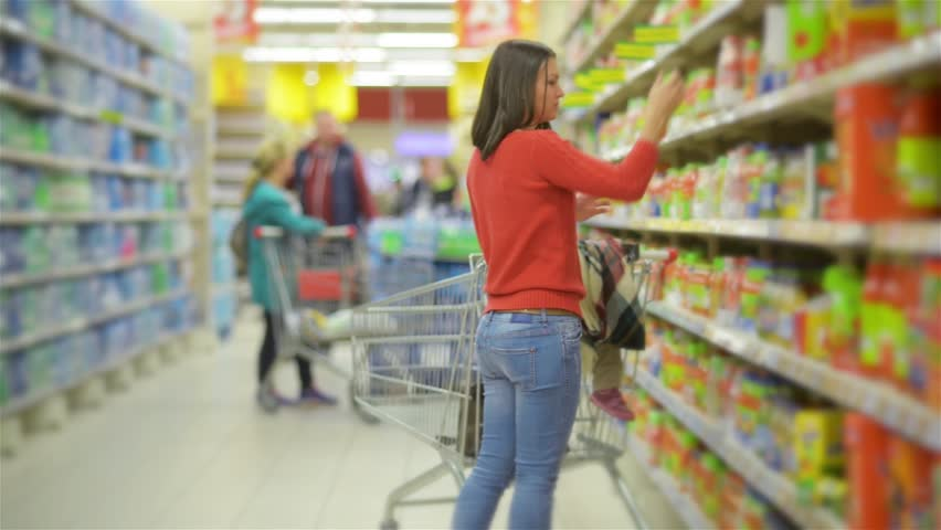 Mother and child walks along wholesale shelves and taking goods in shop trolley, beautiful young wife shopping in a supermarket | Shutterstock HD Video #20495275