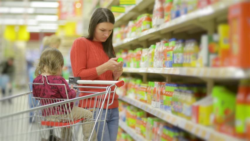 Mother and child walks along wholesale shelves and taking goods in shop trolley, beautiful young wife shopping in a supermarket | Shutterstock HD Video #20495278