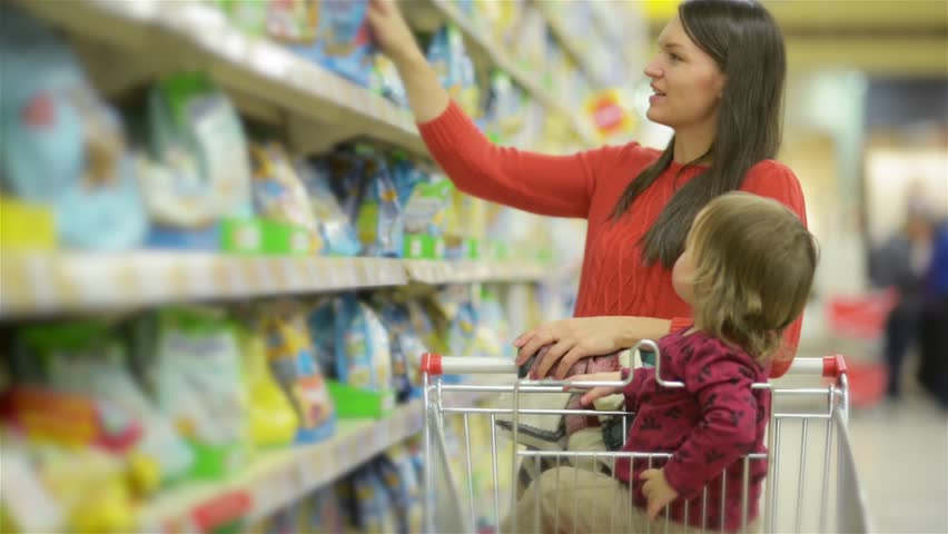 Beautiful woman with baby daughter shopping in supermarket, young Mother chooses food for their child in the market | Shutterstock Video #20534788