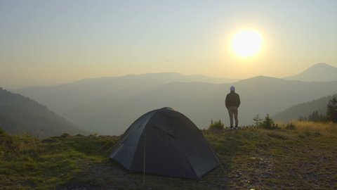2 in 1 video! The man stand near the tent on the background of mountain landscape. Real time capture. Wide angle