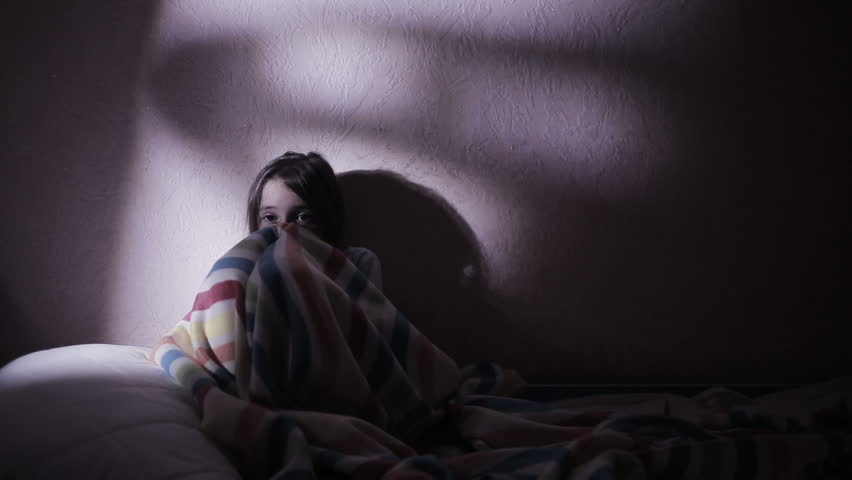 girl under the covers in the night afraid of ghosts. nightmares.