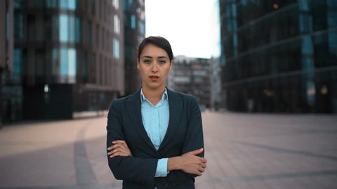 4k. Ultra HD. Portrait of young confident sexy caucasian businesswoman with arms crossed disapproval Your opinion. Pomade, brownhair, lady. Negation concept. Formal suit. Modern glass buildings bg