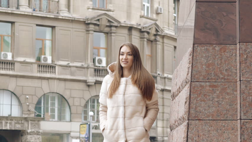 Stylish woman in furry coat walks runway and smiling on the street. Slowly