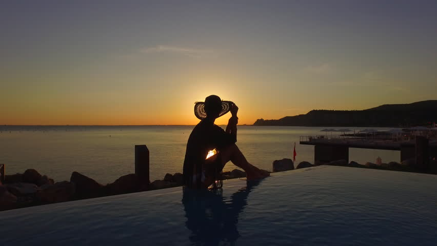 AERIAL, CLOSE UP: Attractive woman sitting on edge of infinity pool, looking at rippling sea and dreamy golden sun setting on the horizon. Sunshine glittering and reflecting on glassy ocean surface