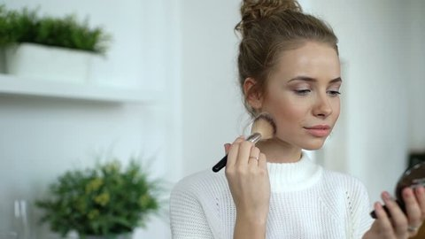 Beauty woman applying makeup. Beautiful girl applying cosmetic with a big brush. Girl gets blush on the cheekbones. Powder, rouge. Slow motion.