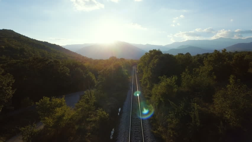 Railroad aerial drone forward motion beautiful countryside railway landscape hilly terrain mountains forest sun light