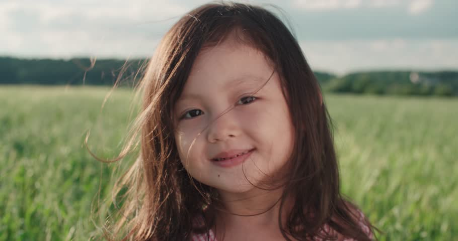 Little Asian girl standing in a green field of young wheat,close-up, flowing hair,slow motion