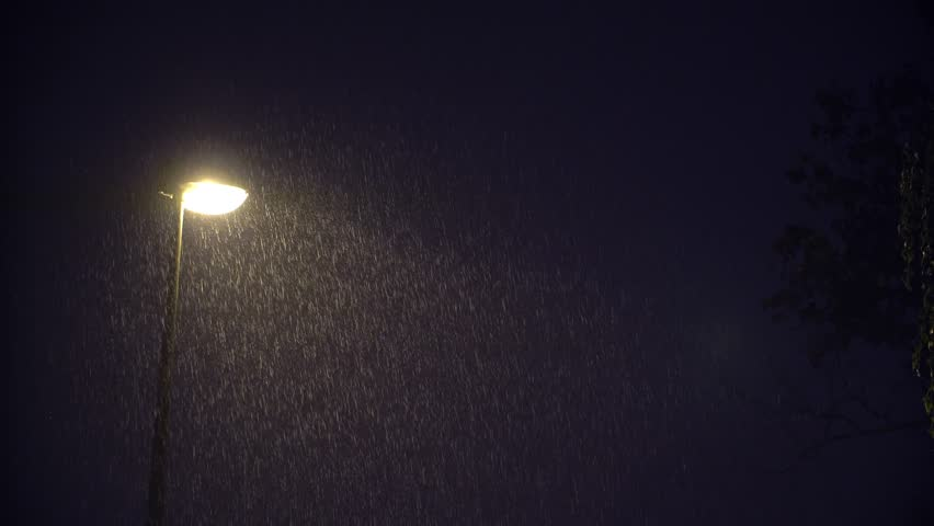 ULTRA HD 4K Illuminated public lamp in dark night and heavy rain, town streetlight
