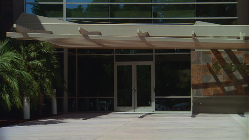 day tight glass doors entrance small long 2 story modern tan brown office building slate tile accents, industrial commercial, corporate park type large windows, small palm trees left pushes in