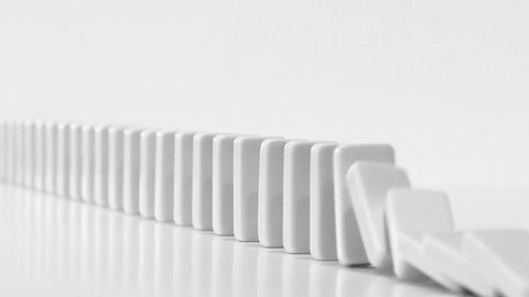 DOMINO EFFECT - white dominoes fall in chain reaction B/W with plenty room for copy