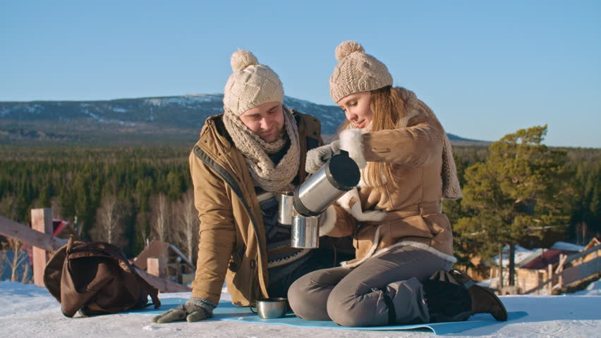 Young man and woman sitting on snow, pouring tea from thermos bottle, kissing and embracing while spending winter day outdoor #20700028
