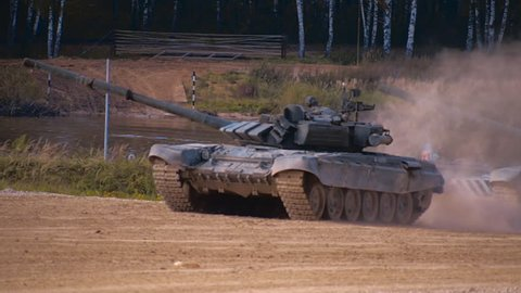 T-90 tanks are driving in a row on a ground road, stir up dust. Includes audio. Contains audio