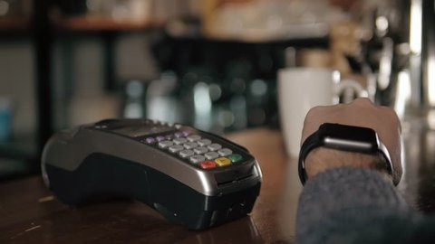Customer paying with NFC technology by smart watch contactless on terminal in modern cafe