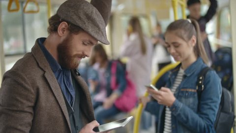 Young man with beard standing in trolleybus and texting someone on tablet, woman communicating on phone in background