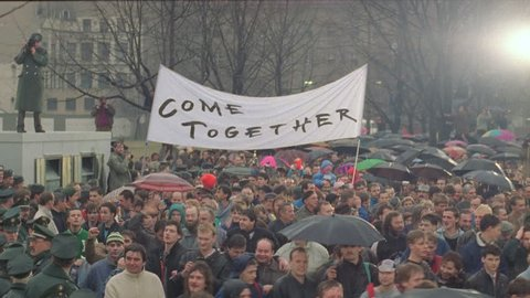 day down crowd celebrating near Berlin Wall, see photo flashes military soldiers, Come Together banner, light rain, fall Berlin Wall, historical footage