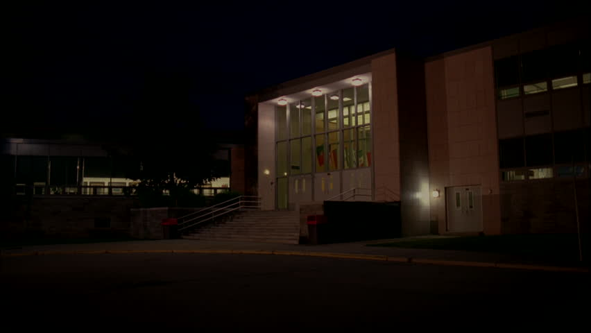 night Tall lit two story high school building stairs front Pan right Up building