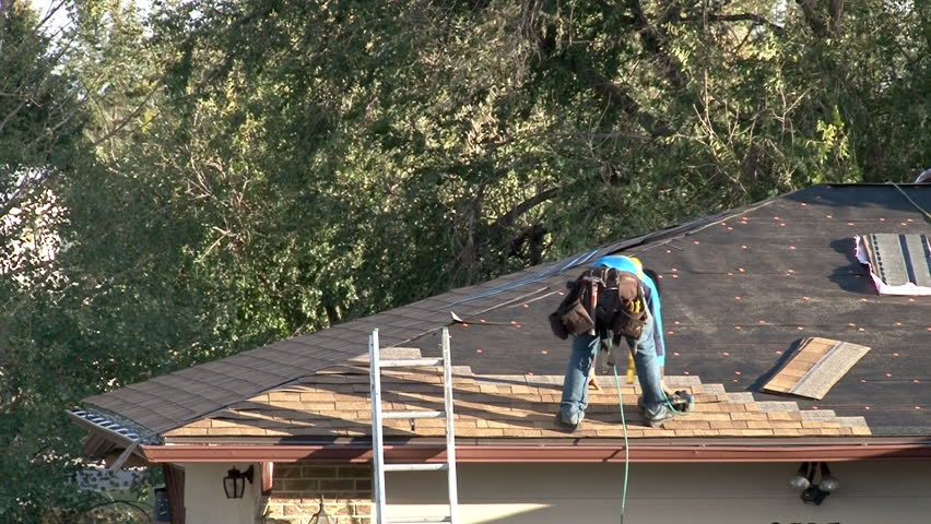 Roofing contractor uses air powered nail gun to install shingles on residential roof. #20752048