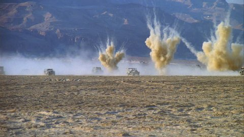 day right large military vehicles jeeps, troop carriers military convoy traveling through middle eastern desert small explosions mortar blasts push last jeep into dust cloud, SPOV back forth