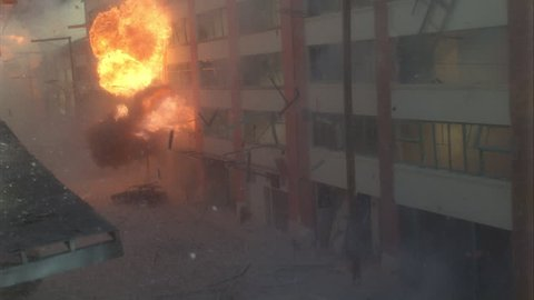 day slight high down large 5 story brick stucco office building warehouse then see large fireball buildings behind then works it way foreground explodes building explosion fire smoke