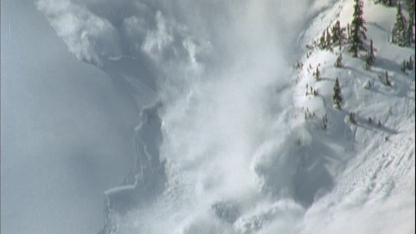 day High angle Steep snow covered mountainside Explosion near top causes avalanche Tilt down over sliding snow Green bare trees Tilt up more avalanche natural disaste right, news footage, playback