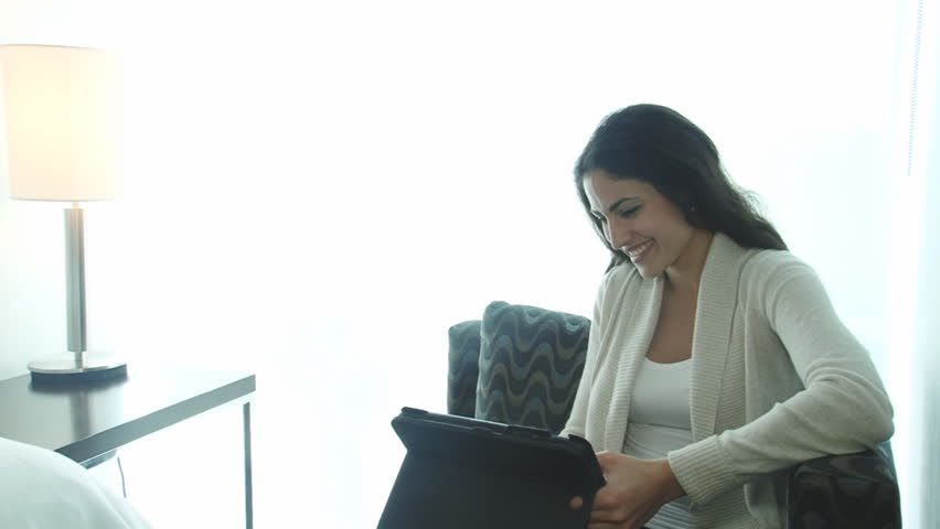 Happy traveling business woman working on tablet in hotel