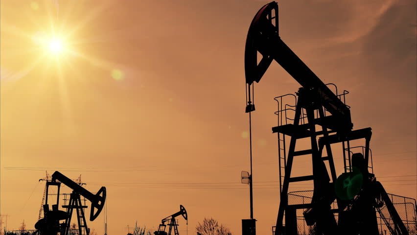 Fracking Oil Well Silhouettes ;  Oil Field with pumps, silhouette against sunset
