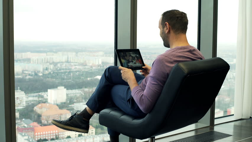 Man watching movie on tablet sitting on chair by window ta home
