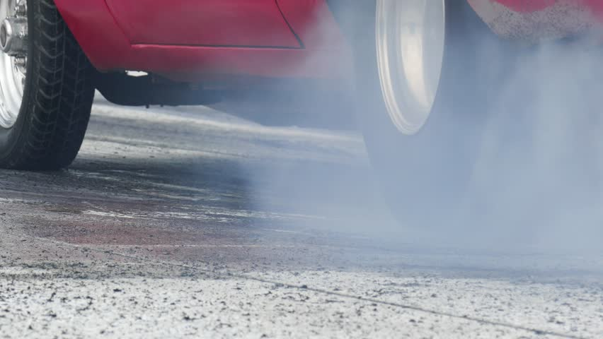 Fiery red drag strip muscle car burning rear wheel rubber while creating white smoke. Also showing a stationary front wheel, and finally nothing but hot asphalt.
