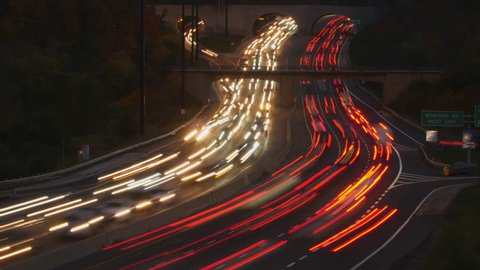 Time lapse of evening traffic. Headlights and brakelights streaking past on the curves of the Don Valley Parkway, Toronto, Canada.