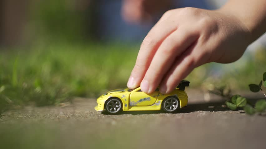 Kid playing with a yellow toy car on the backyard. #20863138