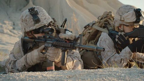 Soldiers Lie Down on the Hill, Aim through the Assault Rifle Scope in Desert Environment. Shot on RED EPIC Cinema Camera in 4K (UHD).