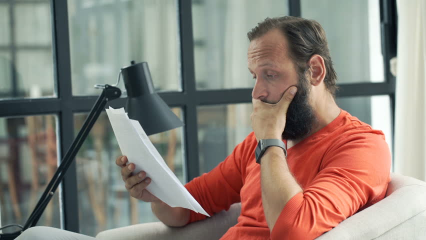 Sad, unhappy man reading bills while sitting on armchair at home  | Shutterstock HD Video #20908528