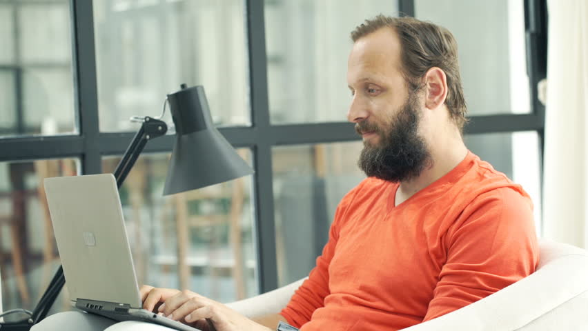 Young man using laptop sitting on armchair at home  | Shutterstock HD Video #20908567