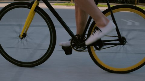 Closeup - Male pedaling fixie bicycle wearing casual men shoes in the city center