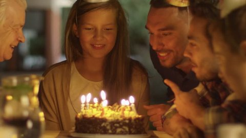 Happy Smiling Girl Blowing Candles out on her Birthday Cake. Girl Surrounded by Her Family and Friends. Shot on RED Cinema Camera in 4K (UHD).