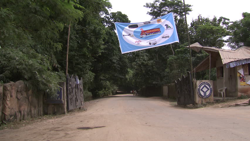 Osogbo, Nigeria - August 2013; Van passes through open gates of the Sacred Grove. Osun Osogbo festival banner.