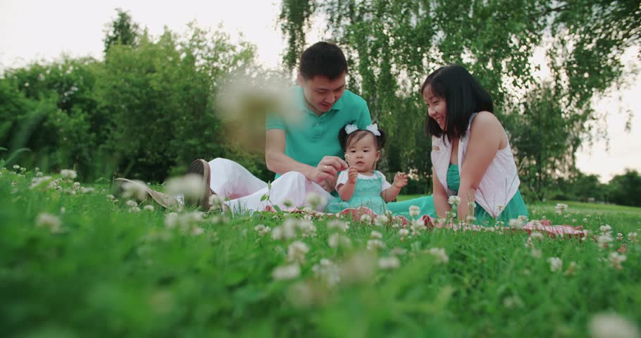 Young Asian family with a year-old baby in a Park during a picnic, have fun, slow motion
