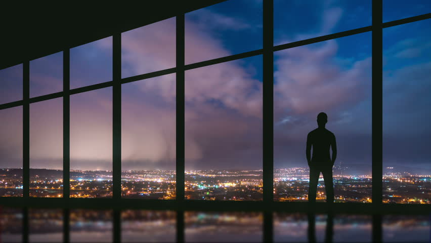 5 in 1 video! The man stand at the panoramic window on the background of night the city. Time lapse. Wide angle