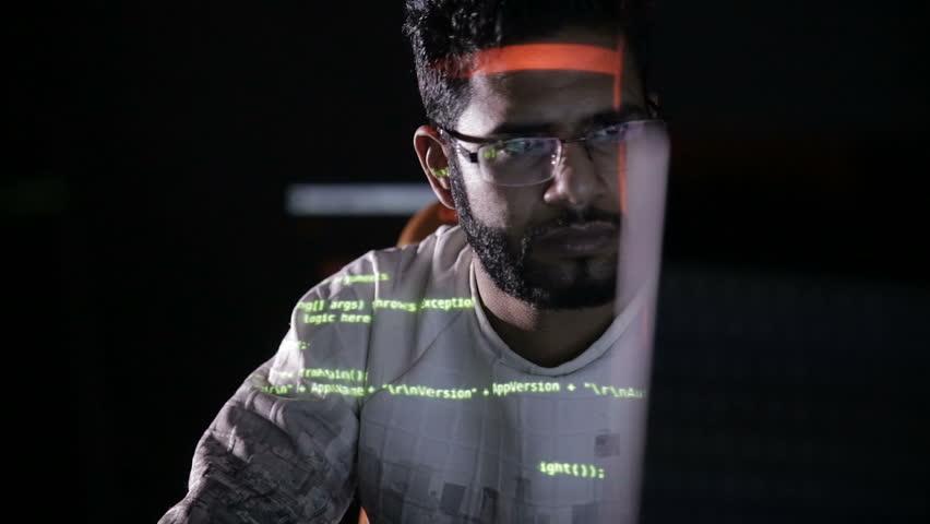 Arabic IT specialist working on computer at night. Hacker breaking computer code.