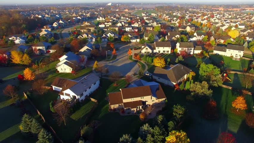 Tranquil idyllic wealthy Autumn neighborhood with frosty rooftops at sunrise, aerial view.