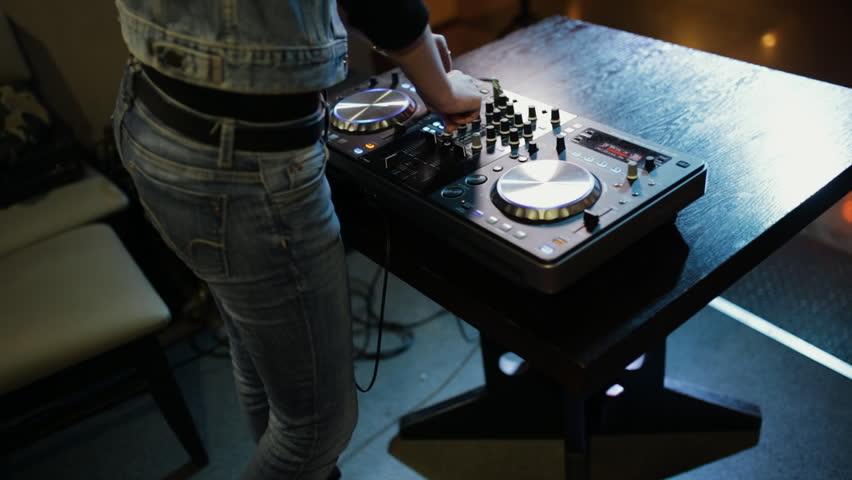 Female hands of DJ tweak track controls on dj's deck, camera is breathing | Shutterstock HD Video #21027328
