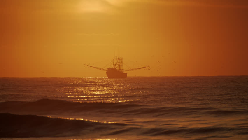 Cinematic shot of a shrimp boat fishing just off shore of South Carolina in the Atlantic Ocean at Isle of Palms just east of Charleston with warm golden early morning cast and heavy natural vignette.