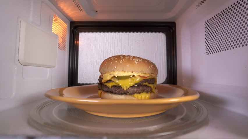 Reheating cooked double cheeseburger hamburger in the microwave. Tasty hamburger topped with cheese two patties and lettuce microwaving inside oven.