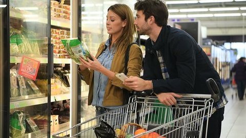 Couple in supermarket reading shopping list on smartphone