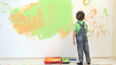 Little child painting the wall, funny boy enjoying to decorate the wall