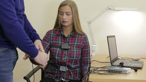 A man puts a woman on the sensors lie detector test
