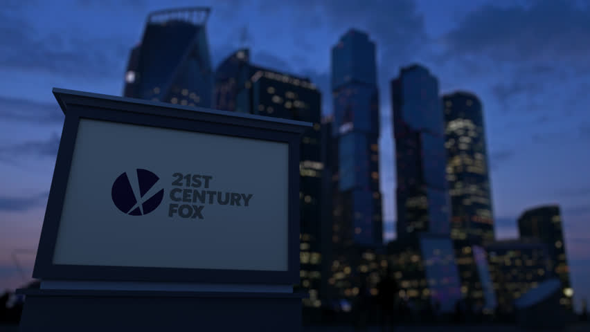 Street signage board with 21st Century Fox logo in the evening. Blurred business district skyscrapers background. Editorial 4K clip