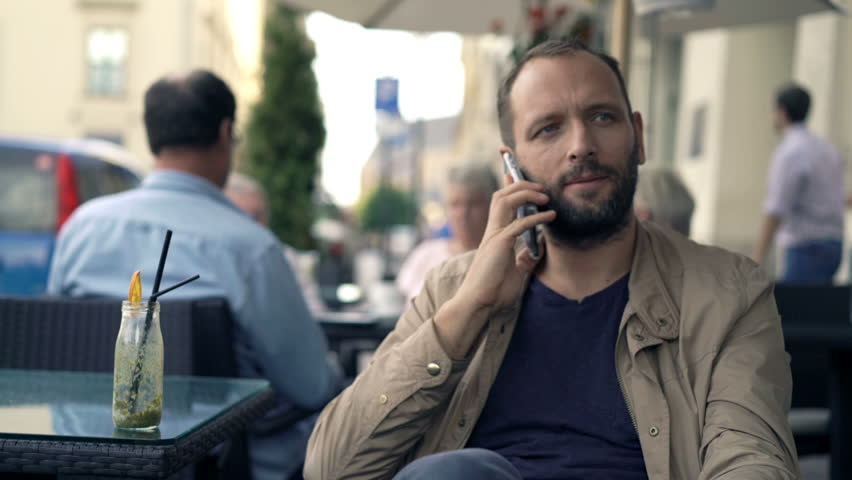 Young man talking on cellphone and drinking cocktail in cafe in city  | Shutterstock HD Video #21229228