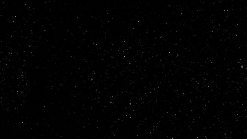 Magic Night Before Christmas. Small white particles flow in the air on a black background to simulate snow, blizzard, or a microcosm of the Christmas magic. Filmed at a speed of 240fps